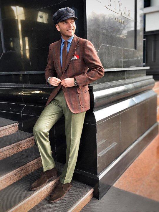 Vyras vilki rusvą švarką, žalias kelnes, avi tamsiai rudus batus