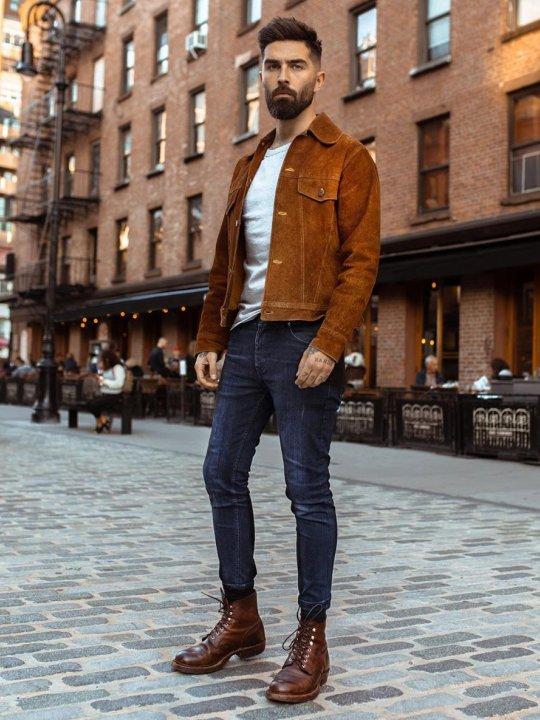 Vyras vilki rudą švarką, tamsiai mėlynus džinsus, avi tamsiai rudus aulinius batus