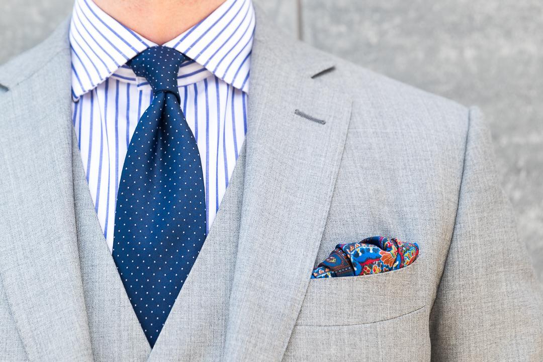 Šviesiai pilkas kostiumas mėlyni marškiniai tamsiai mėlynas kaklaraištis