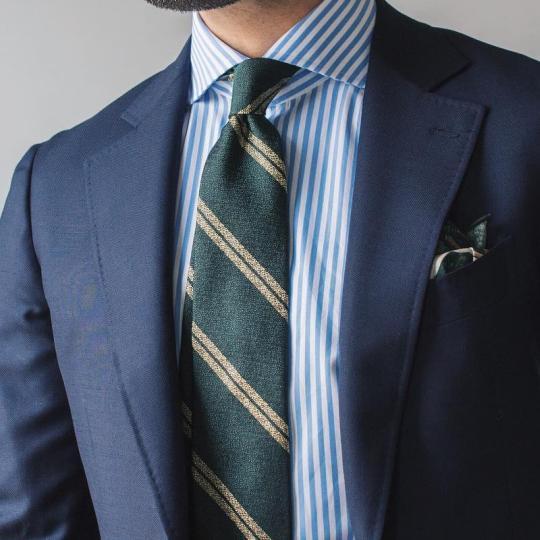 Tamsiai mėlynas kostiumas, šviesiai mėlyni juostuoti marškiniai, tamsiai žalias dryžuotas kaklaraištis