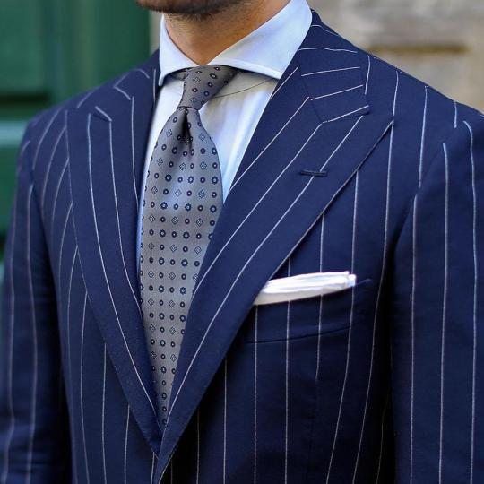 Tamsiai mėlynas juostuotas kostiumas, balti marškiniai, pilkas raštuotas kaklaraištis