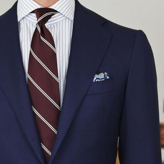 Tamsiai mėlynas kostiumas, šviesiai pilki juostuoti marškiniai, raudonas dryžuotas kaklaraištis
