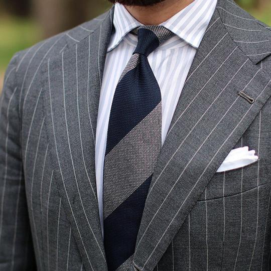 Tamsiai pilkas dryžuotas kostiumas, šviesiai pilki juostuoti marškiniai, tamsiai mėlynas pilkas dryžuotas kaklaraištis