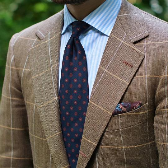 Rudas languotas švarkas, šviesiai mėlyni dryžuoti marškiniai, tamsiai mėlynas taškuotas kaklaraištis