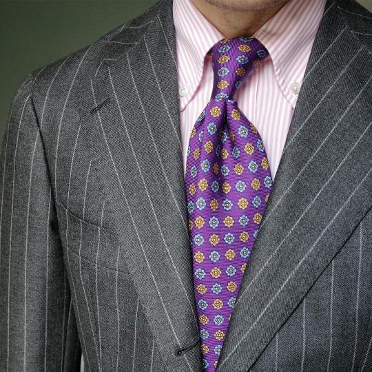 Tamsiai pilkas dryžuotas kostiumas, rožiniai dryžuoti marškiniai, violetinis raštuotas kaklaraištis