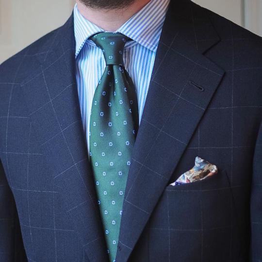 Tamsiai mėlynas languotas švarkas, šviesiai mėlyni dryžuoti marškiniai, žalias margas kaklaraištis