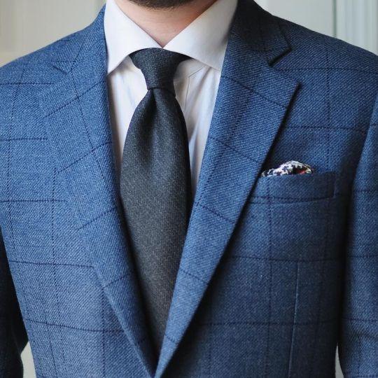 Mėlynas languotas kostiumas, balti marškiniai, tamsiai mėlynas kaklaraištis