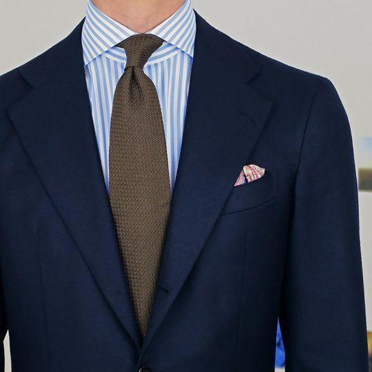 Tamsiai mėlynas kostiumas, šviesiai mėlyni juostuoti marškiniai, rudas kaklaraištis