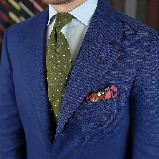 Mėlynas švarkas, šviesiai mėlyni marškiniai, žalias taškuotas kaklaraištis
