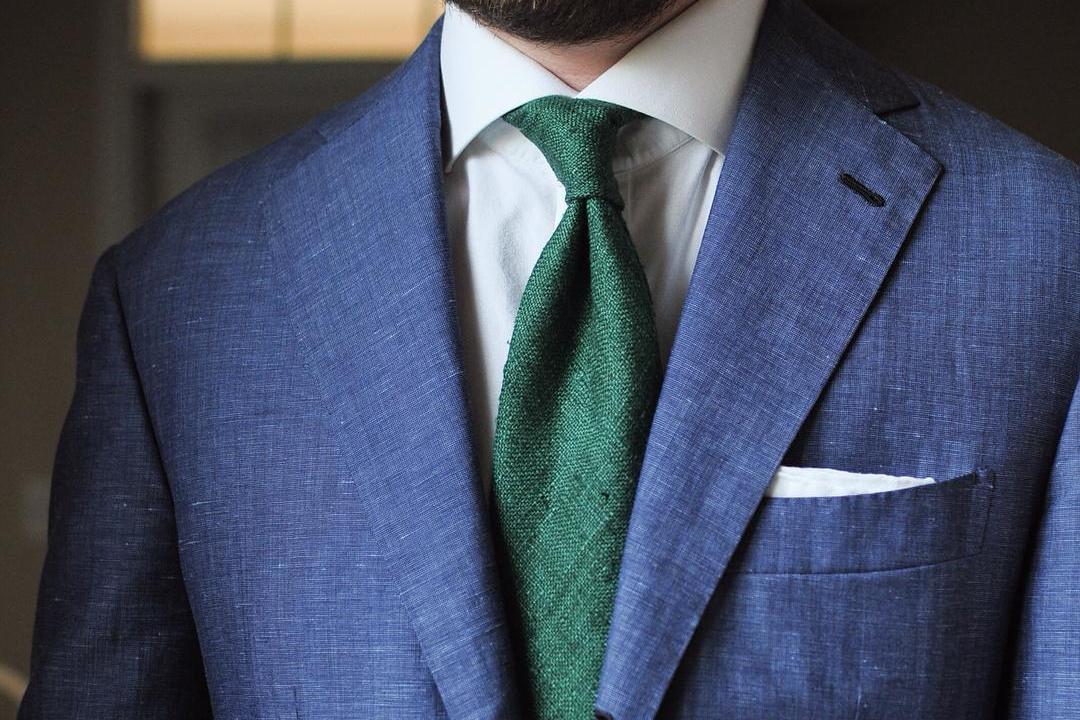 Mėlynas švarkas, balti marškiniai, žalias kaklaraištis