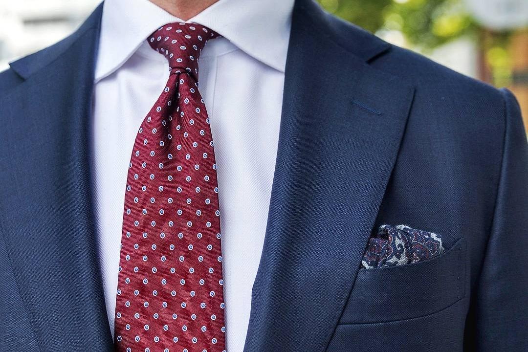 Tamsiai mėlynas kostiumas, balti marškiniai, tamsiai raudonas taškuotas kaklaraištis