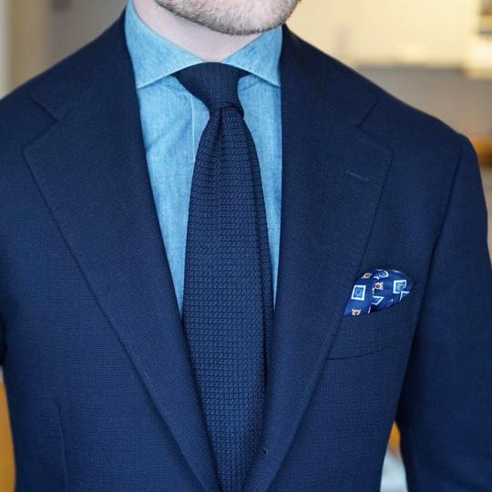 Tamsiai mėlynas kostiumas, šviesiai mėlyni marškiniai, tamsiai mėlynas kaklaraištis