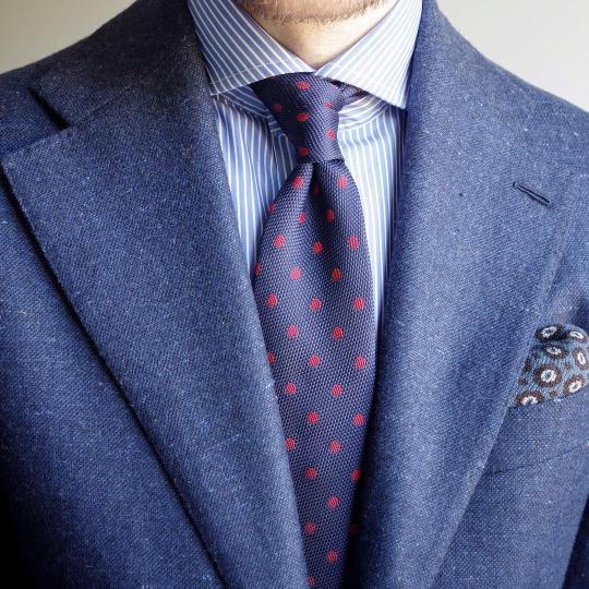 Mėlynas švarkas, šviesiai mėlyni marškiniai, mėlynas taškuotas kaklaraištis