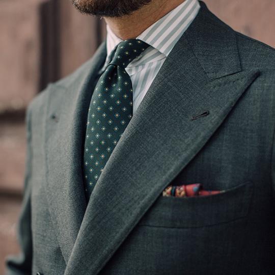 Žalias švarkas, šviesiai žali juostuoti marškiniai, žalias taškuotas kaklaraištis