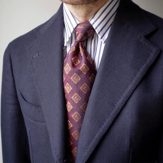 Tamsiai mėlynas švarkas, balti mėlyni dryžuoti marškiniai, violetinis raštuotas kaklaraištis