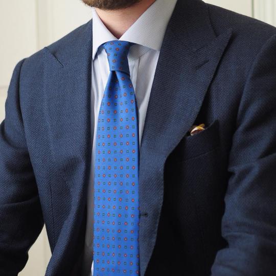 Tamsiai mėlynas kostiumas, balti marškiniai, šviesiai mėlynas raštuotas kaklaraištis