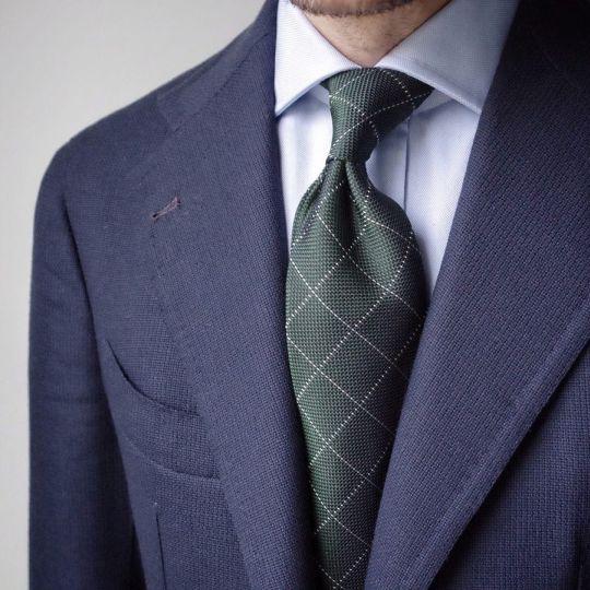 Tamsiai mėlynas švarkas, šviesiai mėlyni marškiniai, tamsiai žalias languotas kaklaraištis