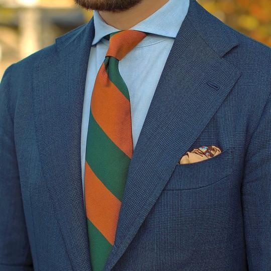 Mėlynas kostiumas, šviesiai mėlyni marškiniai, oranžinis žalias dryžuotas kaklaraištis
