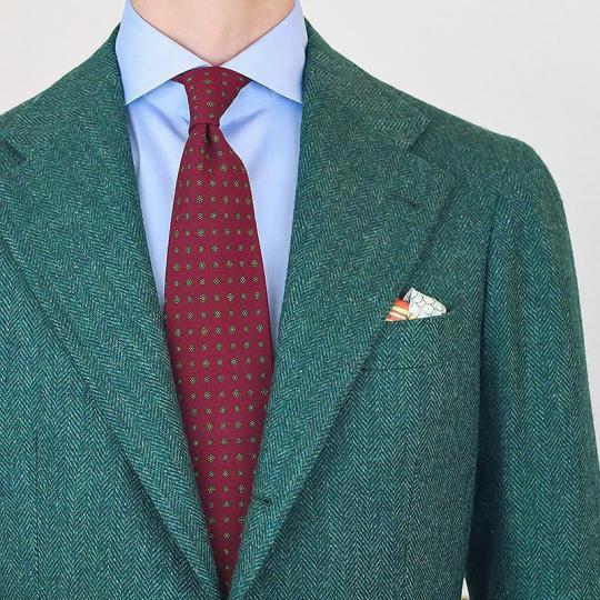 Žalias švarkas, šviesiai mėlyni marškiniai, raudonas taškuotas kaklaraištis