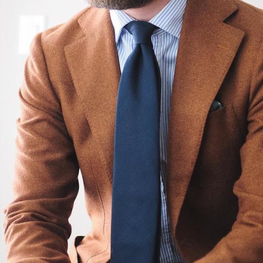 Oranžinis švarkas, šviesiai mėlyni dryžuoti marškiniai, tamsiai mėlynas kaklaraištis