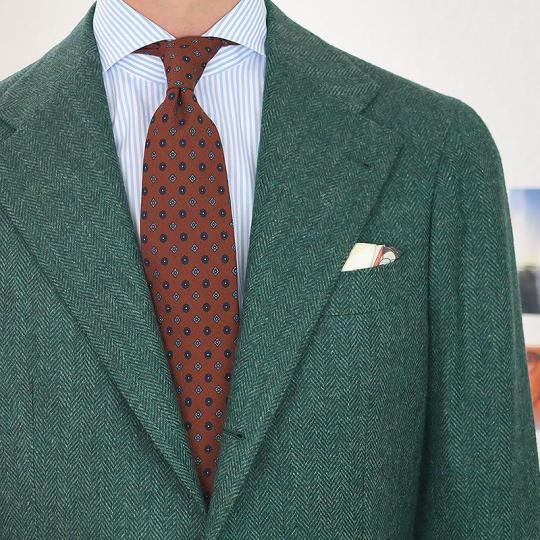 Žalias švarkas, šviesiai mėlyni dryžuoti marškiniai, oranžinis margas kaklaraištis