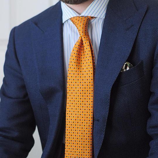 Mėlynas kostiumas, šviesiai mėlyni dryžuoti marškiniai, geltonas margas kaklaraištis
