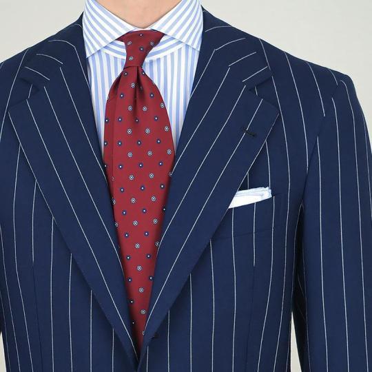 Tamsiai mėlynas dryžuotas kostiumas, šviesiai mėlyni dryžuoti marškiniai, raudonas taškuotas kaklaraištis