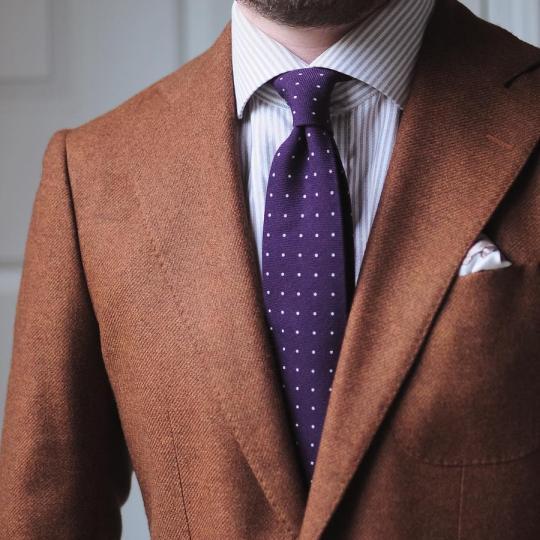 Oranžinis švarkas, šviesiai rudi dryžuoti marškiniai, violetinis taškuotas kaklaraištis