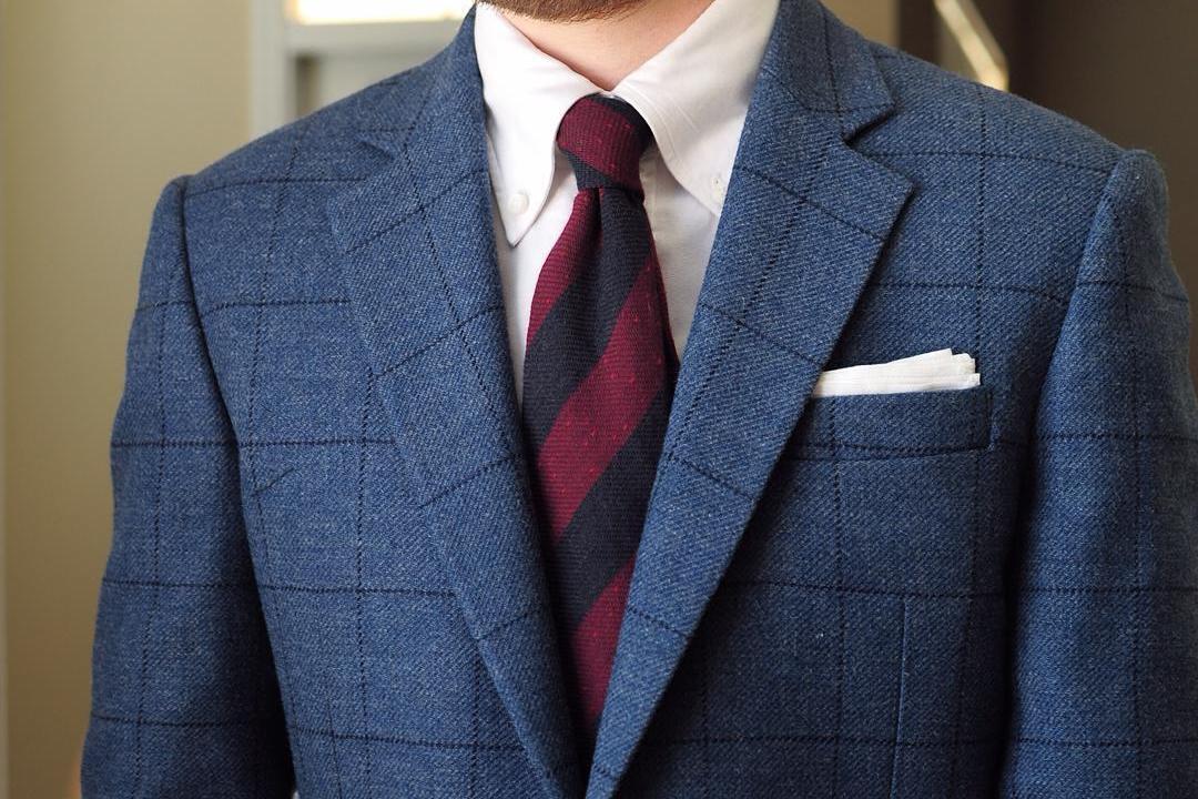 Mėlynas languotas švarkas, balti marškiniai, tamsiai raudonas dryžuotas kaklaraištis