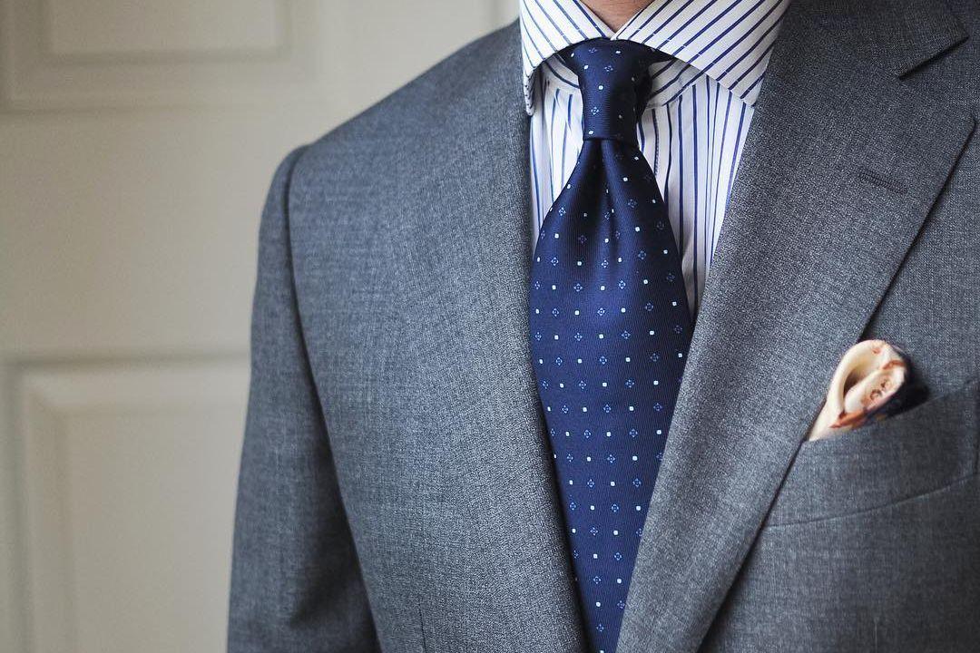Pilkas kostiumas, mėlyni juostuoti marškiniai, mėlynas taškuotas kaklaraištis