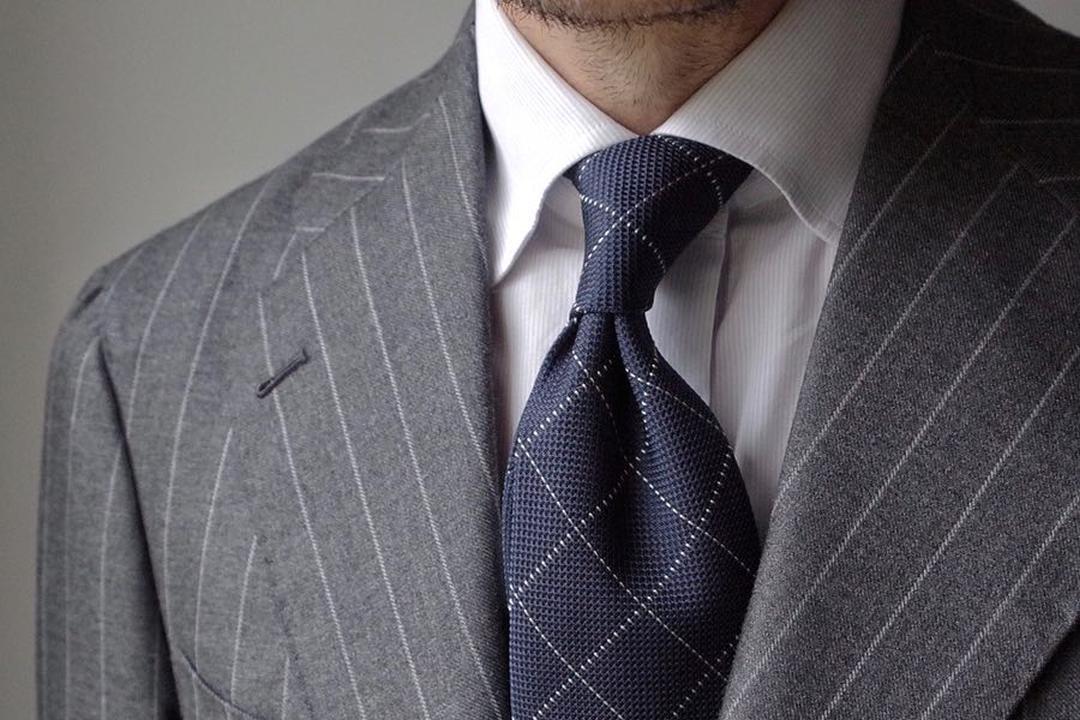 Balti marškiniai, pilkas kostiumas, mėlynas kaklaraištis