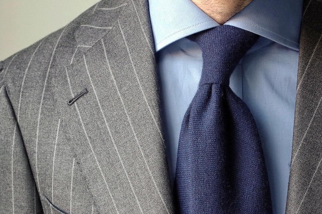 Šviesiai mėlyni marškiniai, mėlynas kaklaraištis, pilkas kostiumas