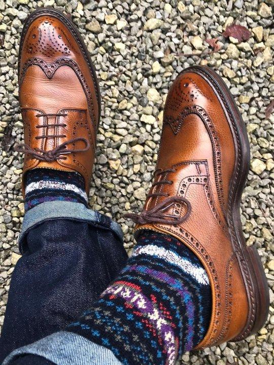 Mėlyni džinsai, mėlynos raštuotos kojinės, rudi batai