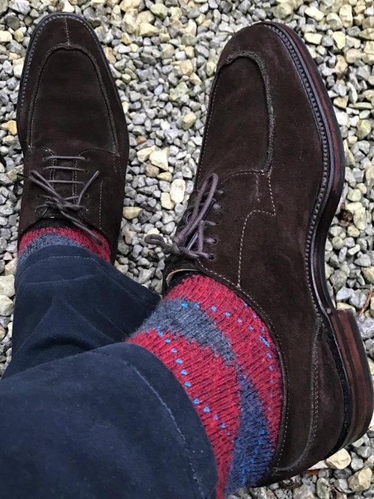Mėlynos kelnės, raudonos raštuotos kojinės, rudi batai