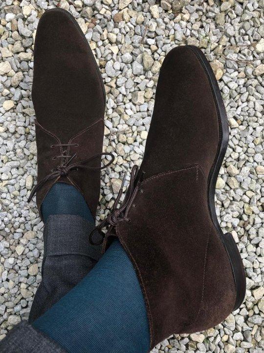 Pilkos kelnės, mėlynos kojinės ir rudi batai