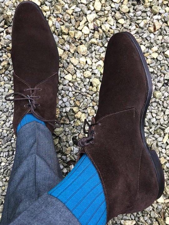 Pilkos kelnės, šviesiai mėlynos kojinės, rudi batai