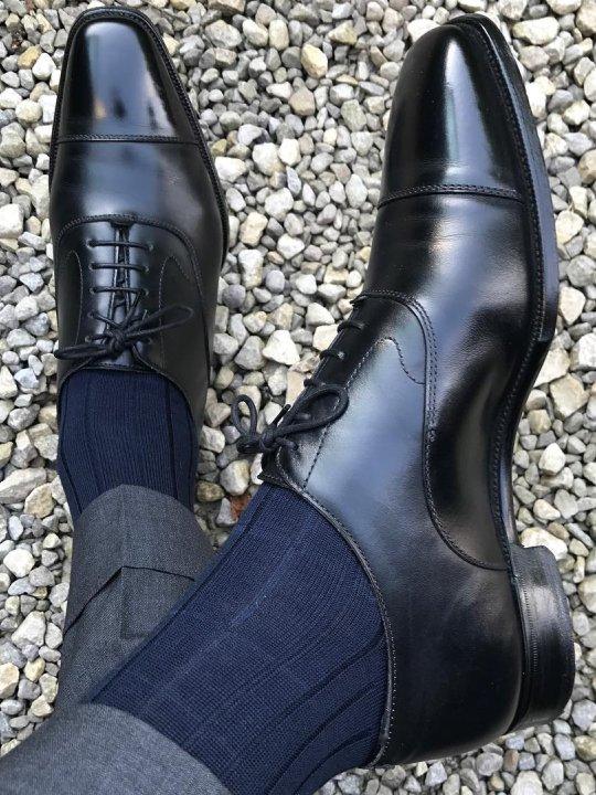 Pilkos kelnės, tamsiai mėlynos kojinės ir juodi batai