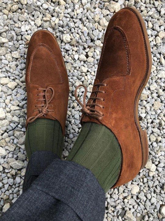 Tamsiai pilkos kelnės, žalios kojinės ir rudi batai
