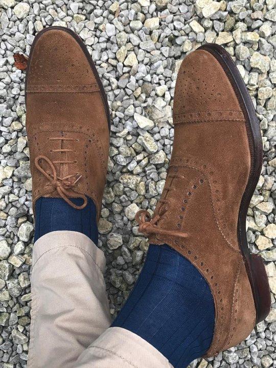 Šviesios kelnės, mėlynos kojinės, rudi batai
