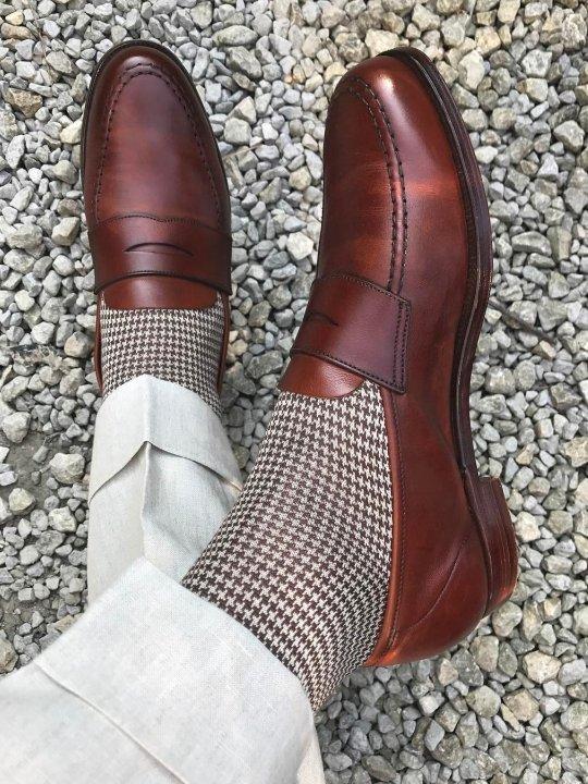 Šviesios kelnės, šviesios kojinės ir rudi batai