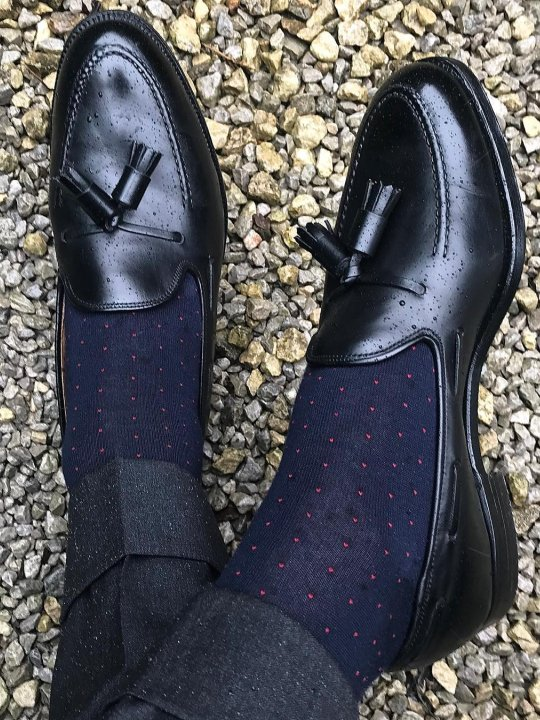 Tamsiai pilkos kelnės, tamsiai mėlynos taškuotos kojines, juodi batai
