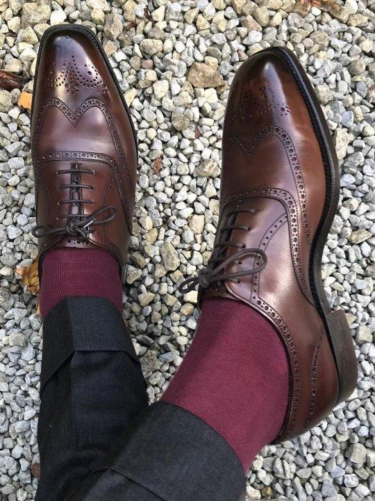 Tamsiai pilkos kelnės, tamsiai raudonos kojinės ir rudi batai