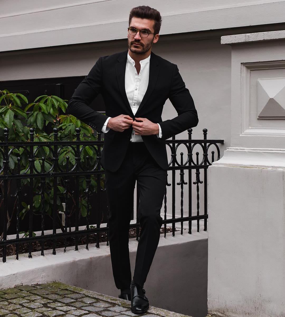 Vyras vilki juodą kostiumą, baltus marškinius avi juodus batus