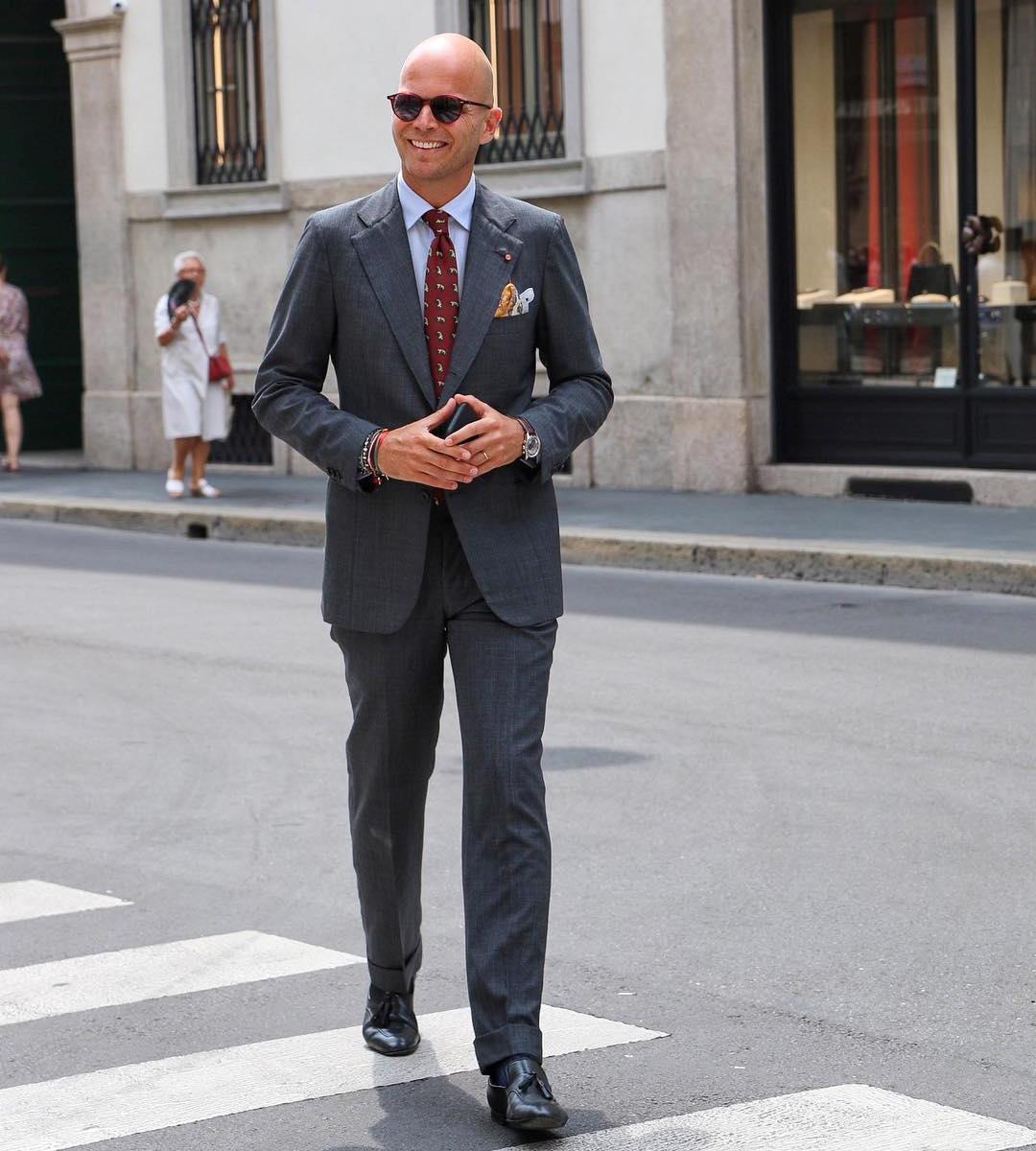 Vyras vilki pilką kostiumą, šviesiai mėlynus marškinius, avi šviesiai rudus batus