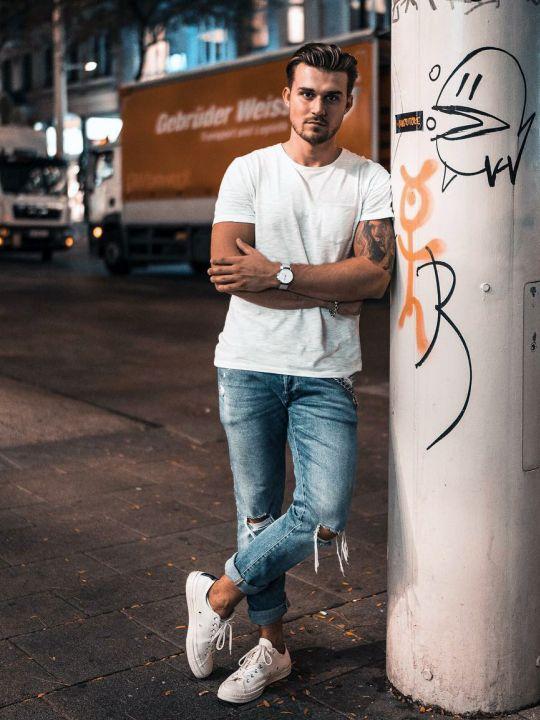 Vyras vilki baltus marškinėlius, šviesiai mėlynus džinsus, avi baltus sportinius batelius