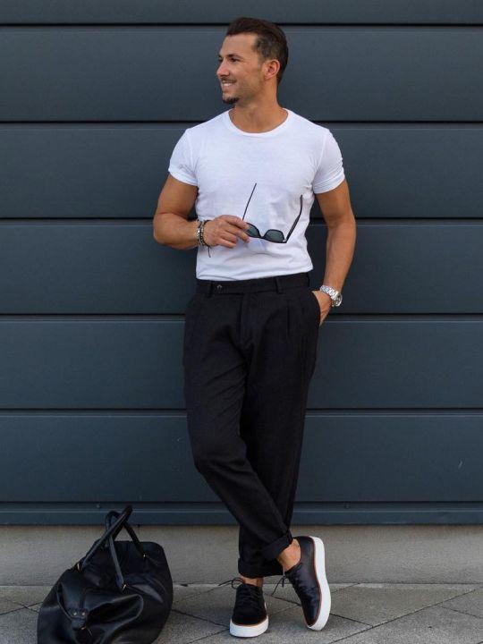 Vyras vilki baltus marškinėlius, juodas kelnes, avi juodus sportinius batelius