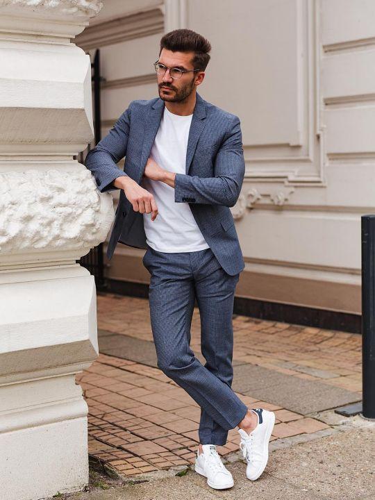 Vyras vilki mėlyną kostiumą, baltu marškinėlius, avi baltus sportinius batelius