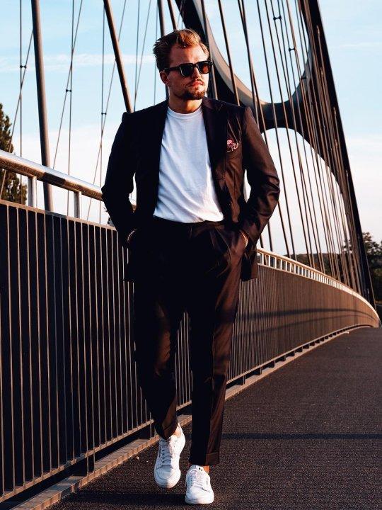 Vyras vilki šviesiai rudą kostiumą, baltus marškinėlius, avi rudus batus