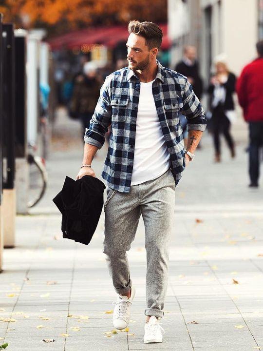 Vyras vilki mėlynus languotus marškinius, baltus marškinėlius, šviesiai pilkas kelnes, avi baltus sportinius batelius