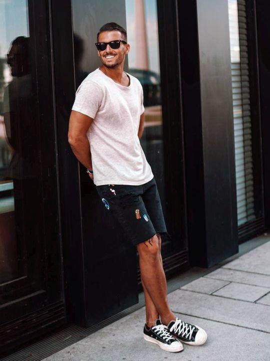 Vyras vilki baltus marškinėlius, tamsiai mėlynus šortus, abi mėlynus sportinius batelius